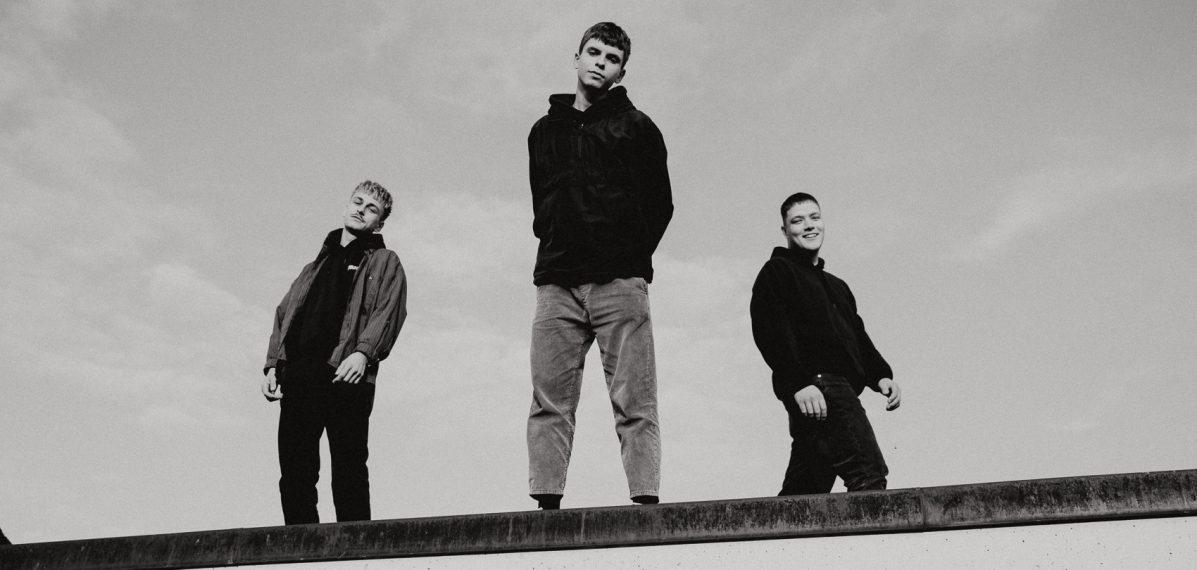 Die drei Jungs der Band VAN HOLZEN stehen auf einem Dach