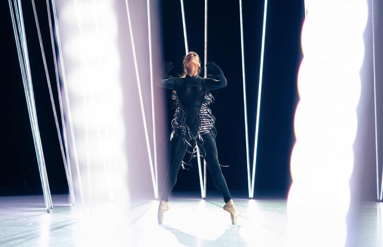 Tänzerin in schwarzem Body vor LED-Röhren